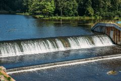 Old dam at ancient hydroelectric power station, water flows. Close up royalty free stock photography