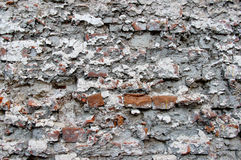 An old damaged brick wall coated with heavily damaged plaster Stock Images