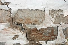 Old damaged brick walll with peeling white plaster. Texture. stock image