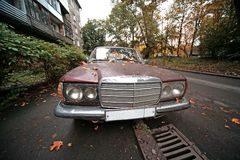 Old damaged car. Old damaged sedan on the city street Stock Images