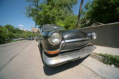Old damaged car. Vintage rusty car on the city street Royalty Free Stock Photography