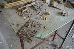 Old damaged dusty soviet electrical circuit boards on the table in abandoned factory of radio components Royalty Free Stock Photos