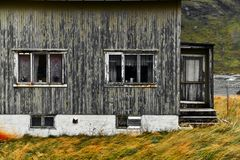 Old damaged facade of a wooden house in the village Vinstad at the coast on Lofoten Islands in Norway. The house is weathered and abandoned with a red roof. It royalty free stock photography