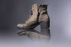 Old, damaged female boots. With gray background royalty free stock photos