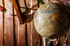 Old damaged globe against wooden wall. Old, damaged, old-style globe against brown  wooden wall, copy space Stock Photography