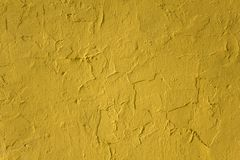 Old damaged peeling yellow concrete wall with cracks and shadows. rough surface texture. A old damaged peeling yellow concrete wall with cracks and shadows royalty free stock photos