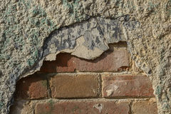 Old and damaged plaster on red brick wall Stock Photography