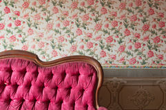 Old damaged red couch in an antique house. Flowers wallpaper in the wall Royalty Free Stock Photos