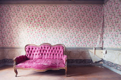 Old damaged red couch in an antique house. Flowers wallpaper in the wall. Old damaged red couch in an antique house. Antique flowers wallpaper in the wall Stock Photography