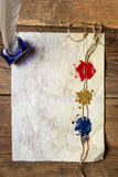 Old damaged sheet of paper with inkwells and three sealing wax. On old wooden table Stock Photos