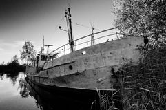 Old and damaged ship on still water Stock Image