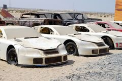 Old damaged sport cars stored in the desert. royalty free stock photos