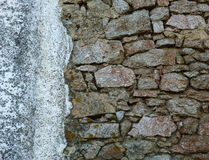 Old and damaged stone wall in decay texture, background. Cracked stone wall, construction in decay, rustic surface Royalty Free Stock Photo
