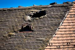 Old damaged tiled roof with a hole on the roof and broken tiles royalty free stock image