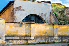 Old damaged wall with a barred window. Old damaged yellow plastered brick wall with a barred window, pavement Royalty Free Stock Photos
