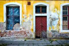 Old damaged wall with barred windows and a door 1 Stock Image