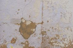 Old damaged wall facade with broken plaster. Close up of vintage damaged plaster wall facade background texture stock photo