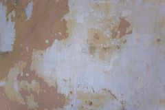 Old damaged white gray concrete wall with pink shabby paint, scratches and cracks. rough surface texture. A old damaged white gray concrete wall with pink shabby stock image