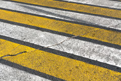 Old damaged white and yellow zebra pedestrian crossing. Royalty Free Stock Images