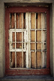 An old damaged window behind metal grating Royalty Free Stock Photography