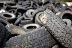 Old Damaged and Worn Out Tires for Recycling. An image of old worn out tires in a landfill waiting to be collected and recycled royalty free stock image