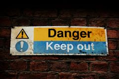 Danger, Keep out sign on a brick wall. An old Danger Keep out sign on a red brick wall royalty free stock images