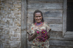 Old Dani tribe lady in Rural area of West Papua. Baliem Valley, West Papua, Indonesia, February 14th, 2016: Dani tribe woman is making a bag royalty free stock photos