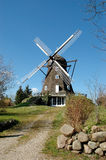 Old Danish windmill. Old Danish mill behind a stone fence and a dusty road Royalty Free Stock Photos