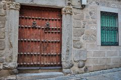 Old dark brown wooden door, two knockers, a windows with grating and green blind in Toledo, Spain. Old dark brown wooden door, two knockers, a windows with Royalty Free Stock Photos