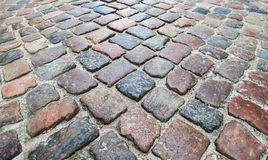 Old dark colorful shining cobblestone road Stock Photography