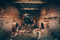 Old dark creepy underground brick tunnel or corridor or sewer pipeline at abandoned ruined industrial factory. Dark retro toned stock image