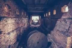 Old dark creepy underground brick tunnel or corridor or sewer pipeline at abandoned ruined industrial factory Royalty Free Stock Photo