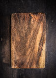 Old dark cutting board on brown wooden table Royalty Free Stock Images