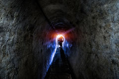 Old dark endless tunnel in the mountains with the figure royalty free stock images
