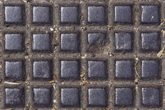 Old dark metal manhole texture with square pattern, background macro, selective focus Stock Photo