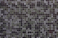 Old dark mosaic tile wall background. Texture close up Stock Images