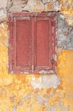 Old dark red wooden window on concrete broken textured house wall. Painted Stock Images