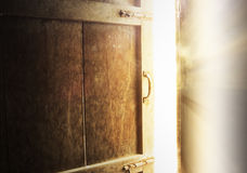 Old dark room with shining closed door. Royalty Free Stock Photos