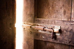 Old dark room with shining closed door. Royalty Free Stock Photo