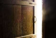 Old dark room with shining closed door. Royalty Free Stock Image