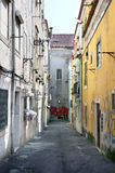 Old dark street in the depth of Lisbon city Royalty Free Stock Photos