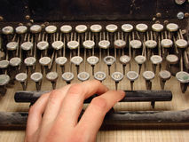 Old dark typewriter with hand Royalty Free Stock Images