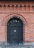 The old dark wooden door in the red brick house Stock Image