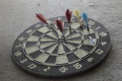 Old Dartboard. Old, heavily used dartboard with five darts in it laying flat on a concrete floor; saturation has been lowered to give it a drab, grungy look Stock Photography