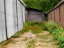 Old dead end alley. Old dirt and gravel empty dead end alley with tall weeds, trees, and sides of old buildings stock photo