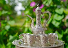 Old decanter and glasses from silver. And green leaves on background Royalty Free Stock Photos