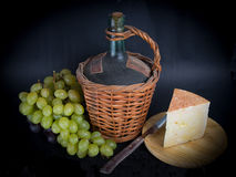 Old Decanter of Red Wine with Grapes and Cheese. On Black Stock Image