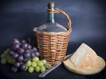 Old Decanter of Red Wine with Grapes and Cheese. On Black Stock Photo