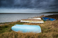 Old decayed rowing boats on shore of lake with stormy sky overhe Royalty Free Stock Photo