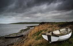 Old decayed rowing boats on shore of lake with stormy sky overhe Stock Image